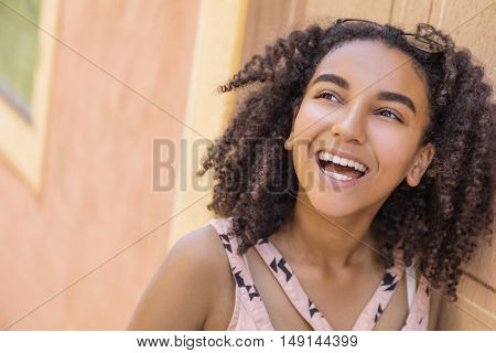 Outdoor portrait of beautiful happy mixed race African American girl teenager female young woman smiling with perfect teeth