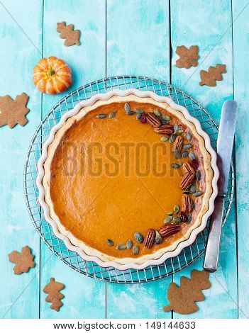 Tasty pumpkin pie, tart made for Thanksgiving day in a baking dish on a cooling rack. Turquoise wooden background