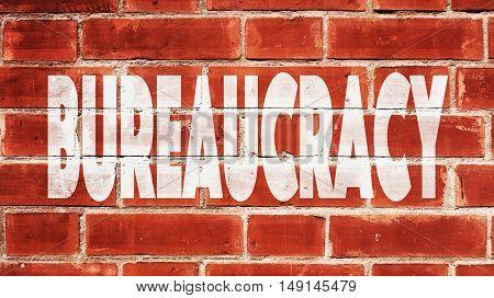 Bureaucracy Written On A Red Brick Wall.