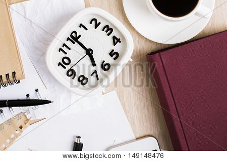 Top view of wooden office desktop with clock coffee cup hardcover book and supplies