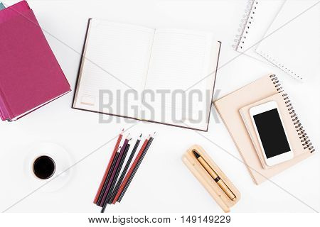 Top view and close up of white office desktop with blank notepad other supplies cellular phone and coffee cup. Mock up