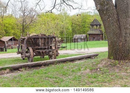 Old wooden wagon parked in rural village landscape