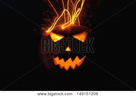 Jack-o ' - lantern scary shining eyes in the darkness. Pumpkin spewing sparks. The Eve Of Halloween