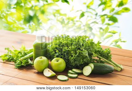 healthy eating, food, dieting and vegetarian concept - bottle with green juice, fruits and vegetables on wooden table over green natural background
