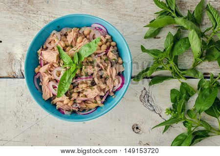 Tuna salad with white beans and red onions in a bowl with basil leaves on white old wooden background. Freshly made tuna and bean salad. Rustic style. Italian cuisine concept. Healthy food. Top view.