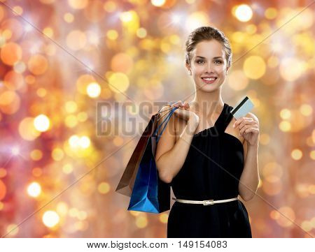 sale, christmas and holidays concept - smiling woman in dress with shopping bags and credit card over lights background