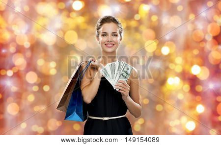 christmas, sale, people, money and holidays concept - smiling woman in dress with shopping bags and money over lights background