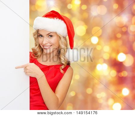 christmas, people, holidays and advertisement concept - happy woman in santa helper hat pointing finger to blank white board over lights background