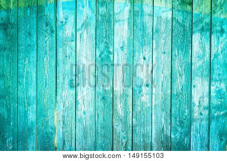 Old blue wood planks background with peeling paint - Vintage wall with vertical boards turquoise color and vignetting effect