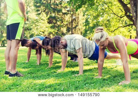 fitness, sport, friendship and healthy lifestyle concept - group of happy teenage friends or sportsmen exercising and doing push-ups at boot camp