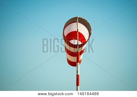 Horizontally flying windsock (wind vane) with blue sky in the background.