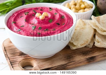 Beet hummus and ingredients on white wooden background
