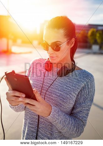 Young woman with headphones choosing song on tablets playlist in sunset