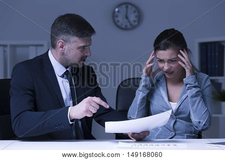 Shot of a boss screaming at a young overwhelmed worker
