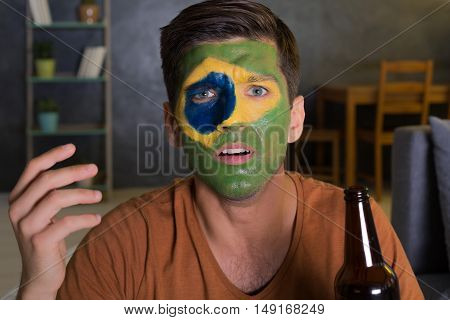 Portrait of a disappointed Brasilian football fan holding a beer