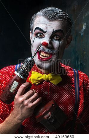 The scary clown and electric drill on dack. Halloween concept of horror and murderer
