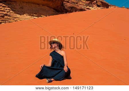 Photo of the Fashion girl in stylish hat sunglasses and long dress enjoying solitude. Inspiration travel mental health retreat concept