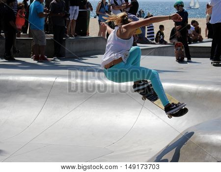 Los Angeles, California, 9/3/2016-- Teen girl on skateboard launches into the air at Venice Beach Skate Park while listening to music on her phone on Labor Day Weekend. Venice Beach is where extreme skateboarding started.