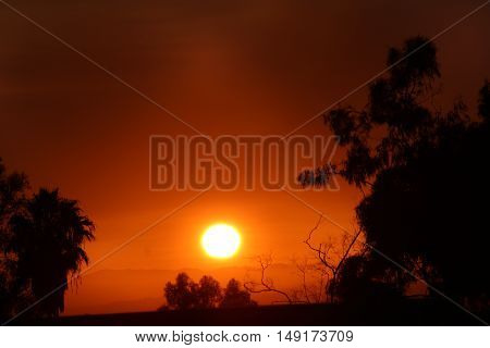 Santa Barbara, California, 8/19/2016--Wildfires burning near Santa Ynez, California turn a sunset over the ocean orange and brown with haze. A record number of brush fires burned all over California over the summer of 2016 as possible indicator of climate