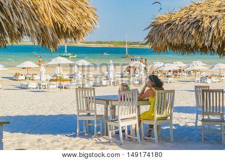JERICOACOARA, BRAZIL, DECEMBER - 2015 - Adult woman sit lonley at outdoor restaurant in Lagoa do Paraiso beach in Jericoacoara Brazil