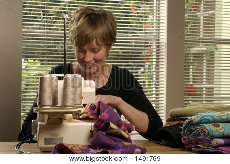 Baby Boomer Sewing At Home On Serger