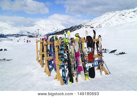 Les Arcs Alps France - March 13 2016: Skis and snowboards left on wooden stand on ski slopes near lifts in French Alps on a cloudy winter day