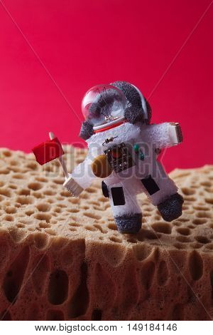 Walking astronaut, red planet Mars background. Light bulb character dressed in spacesuit and spaceman ammunition. Cosmonaut with flag at the edge planet landscape. cosmos exploration concept. Vertical