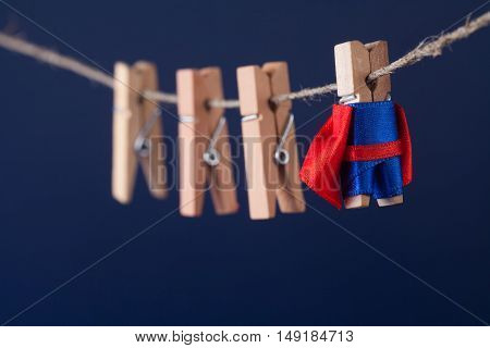Powerful super hero conceptual photo with superstar clothespin character in blue suit red cape. leadership and wooden clothespins team at work. Dark blue background.