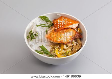 Cellophane glass noodles bowl with a piece of fried meat and vegetables. dish on a gray background, close-up. horizontal photo
