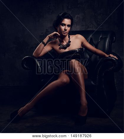 Sexy Woman In Fashion Dress Posing In Necklace Sitting In Luxury Black Armchair And Looking. Dark Dr