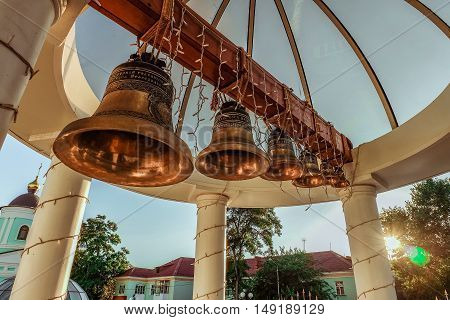 BELGOROD RUSSIA - September 10 2016: Bell tower under the vault of the dome in the Belgorod Orthodox metropolitan. A number of different-sized bells on the background of the low evening sun.