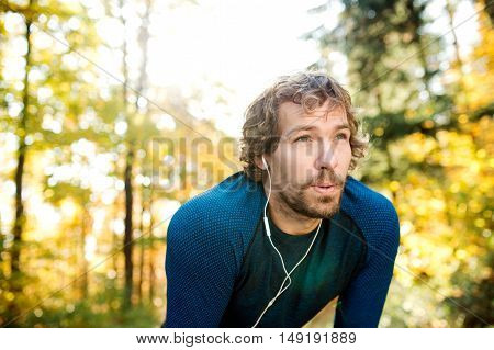 Young handsome runner with earphones in his ears, listening music, outside in sunny autumn nature, resting, breathing out