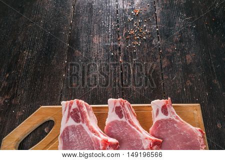 Raw porkchops with spices on the dark wood