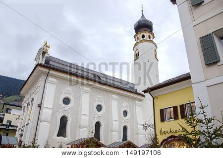 Brunico Italy 14 December 2014: the side of the main church of San Candido classical architecture of Tyrol areas