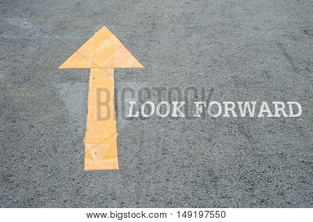 Closeup yellow painted arrow sign on cement street floor with white look forward word textured background