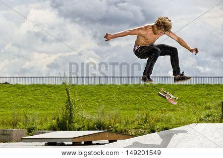 Boy doing skateboard trick 360flip in skatepark