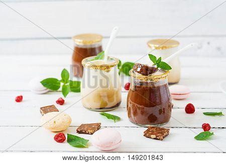 Chocolate and vanilla panna cotta (dessert) on wooden whte table