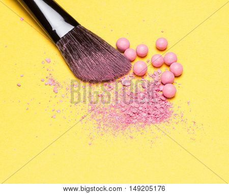 Close-up of makeup brush with crushed and whole shimmer blush balls pink color on yellow background