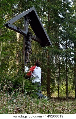 Walker kneels in forest road praying in a cross