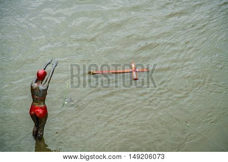 Statue and drifting objects. Skopje, Macedonia - September 25, 2016: Statue and drifting wooden cross in the flooded river Vardar Macedonia. Statue and drifting wooden cross.