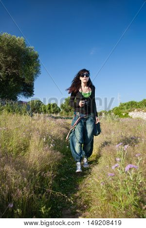 brunette woman with sunglasses black sweater and wide blue jeans trousers with camera hanging walking on field in Menorca Balearic Islands Spain Europe