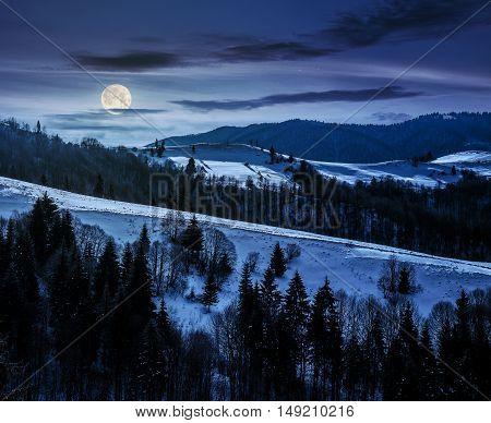 mountainous rural area of Carpathians in winter on fresh frosty night in full moon light