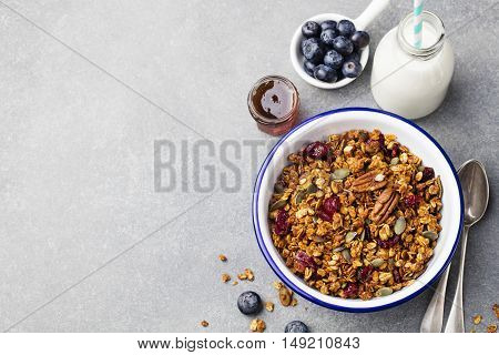 Healthy breakfast. Fresh granola, muesli with pumpkin, pecan nuts, cranberries and maple syrup in white bowl. Copy space. Top view