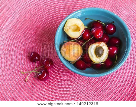 fresh cherries and apricot in green bowl on a pink wicker place mat. Refreshing background