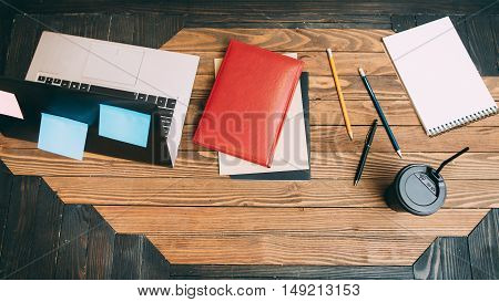Top view on the freelancer workplace. Wooden office desk of a clerk with laptop, some stationery and coffee to go cup. Flat lay business set