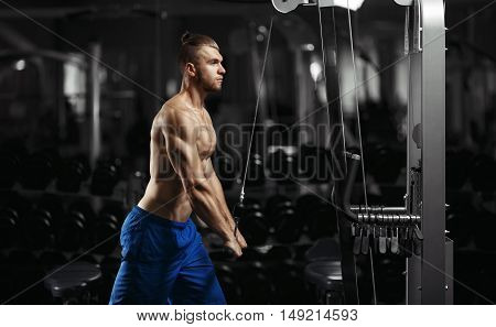 Bodybuilding. Muscular fitness man doing exercises in the gym. Fitness - concept of healthy lifestyle. Fitness man in the gym. Bodybuilder man in the gym.