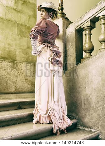 19. century lady posing on stairs, retro style