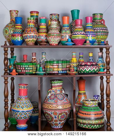 Group of colorful painted pottery vases stacked in wooden storage shelves over white wall