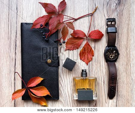 Closeup of men's accessories and essential items on wooden background. Decorated with autumn red leaves. Flat lay top view view from above