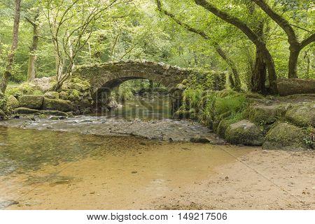 An image of an ancient packhorse bridge over the River Bovey Dartmoor Devon England UK
